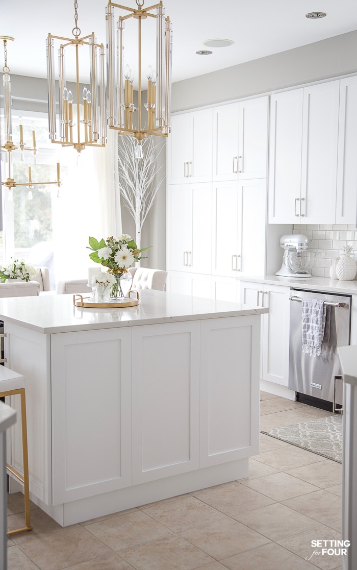 White kitchen island with quartz countertop and two pendant lights over the island. #kitchen #island #pendant #lighting #countertop