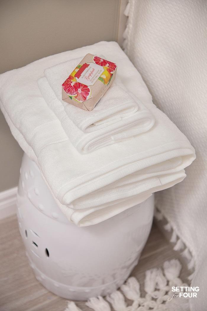 White bath towels stacked on a garden stool. Tassel shower curtain. Tassel bath mat. #bathroom #decorideas #interiordesign #refresh