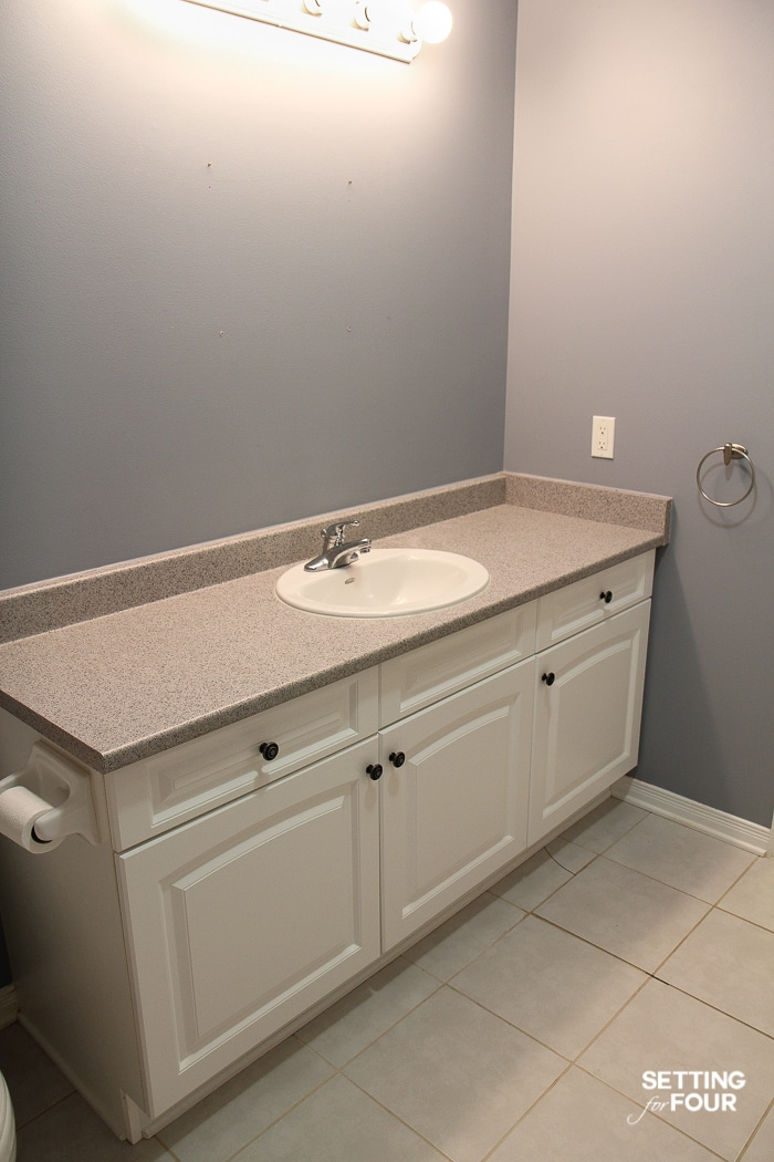 Dark bathroom with white vanity cabinet and Hollywood vanity lights. Cracked floor tile.