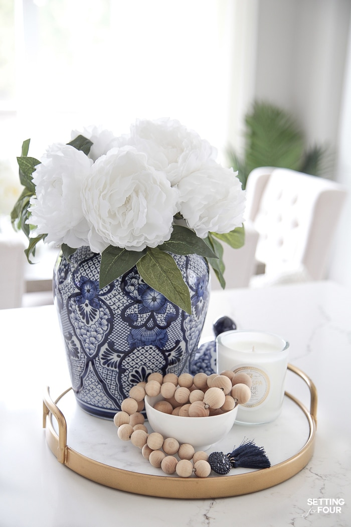 Gold and marble tray decorated with a blue and white ginger jar in a chinoiserie pattern filled with white peonies and Wood bead garland and a white candle.