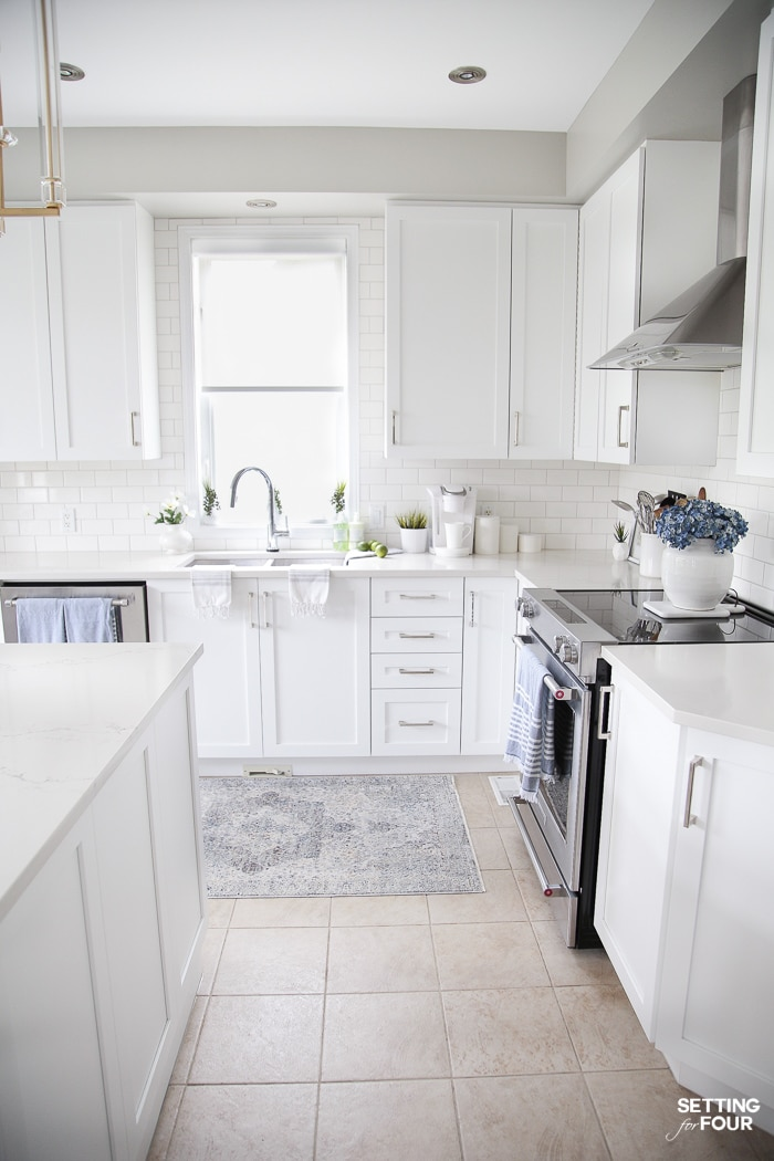 Kitchen with white cabinets, blue rug in front of sink and blue tea towels.