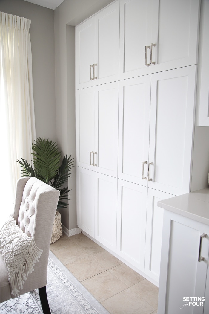 Floor to ceiling white builtin pantry cabinet doors in a white kitchen.