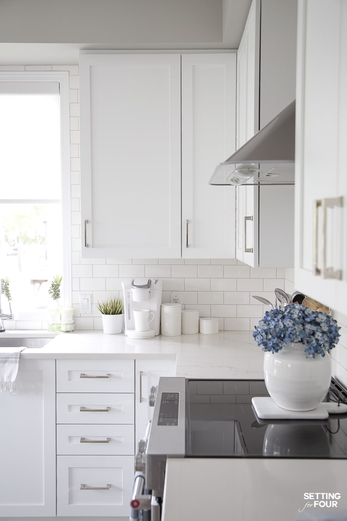 WHite keurig coffeemaker and white kitchen canisters on caesarstone countertops. White kitchen cabinets. Blue hydrangeas. White vase. Kitchenaid electric range with flat ceramic cooktop