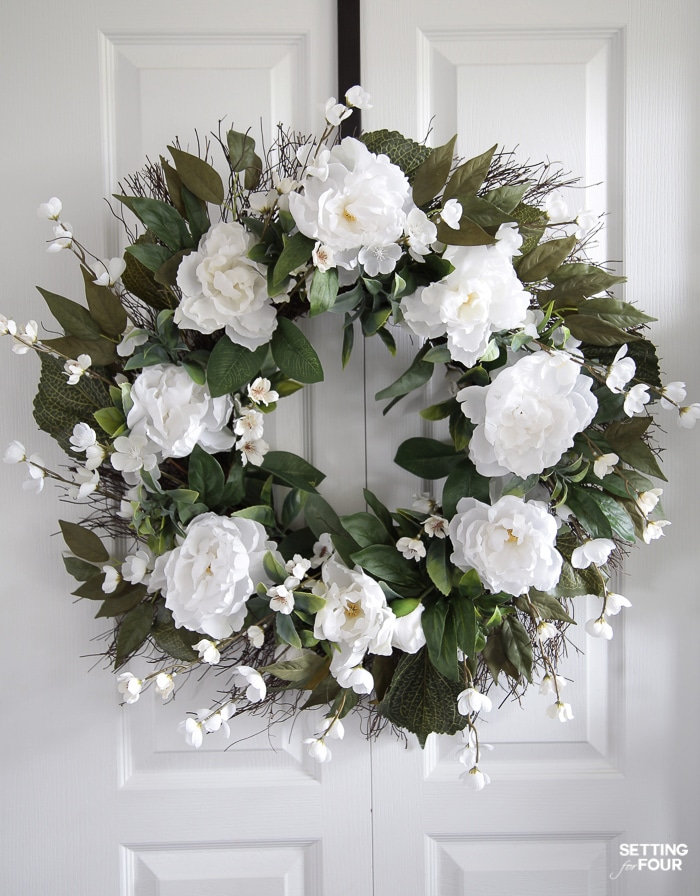 Peony floral wreath hung on a door.
