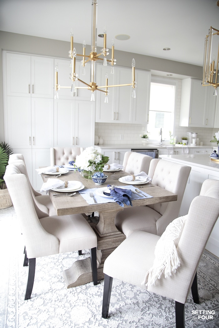 White kitchen with brass and crystal chandelier and rustic farmhouse table.