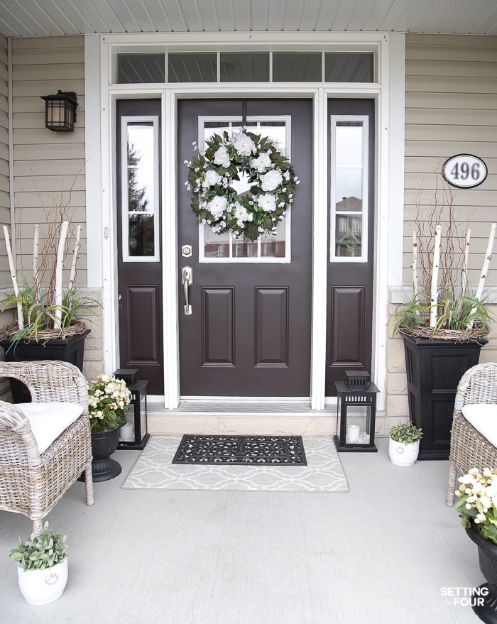 Front porch decorated for summer with a large peony wreath hung on the front door and large urns filled with ferns and birch branches.
