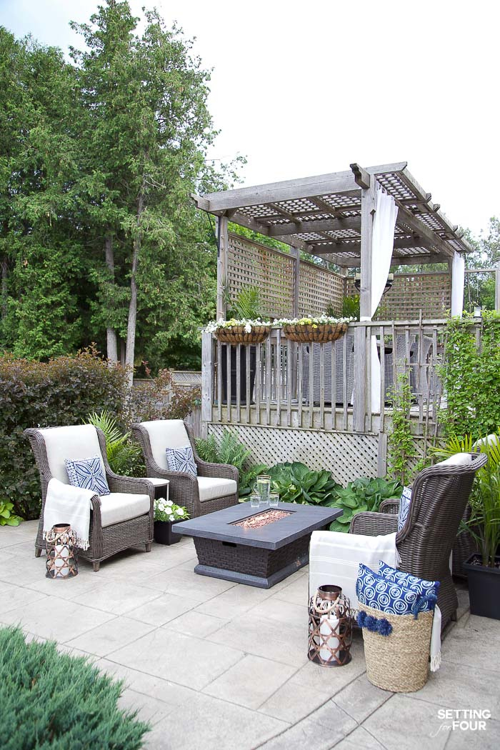 Backyard patio seating area with fire table and hosta plants in a landscaped backyard.