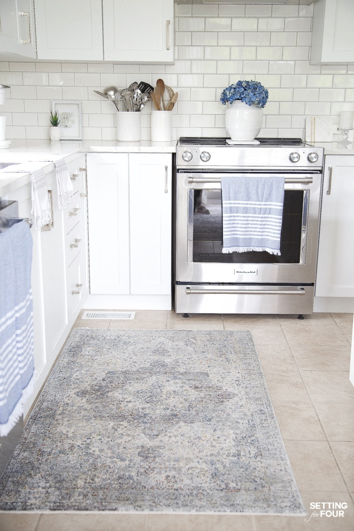 Kitchen with white cabinets. White subway tile with gray grout. Blue and white medallian kitchen runner rug. Blue tea towels. Blue hydrangeas in a white vase.