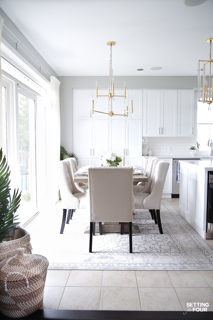 Dining area decorated for summer with blue and white tablescape. Gold and crystal chandelier hanging over gray wood dining table. Gray rug and upholstered dining chairs.