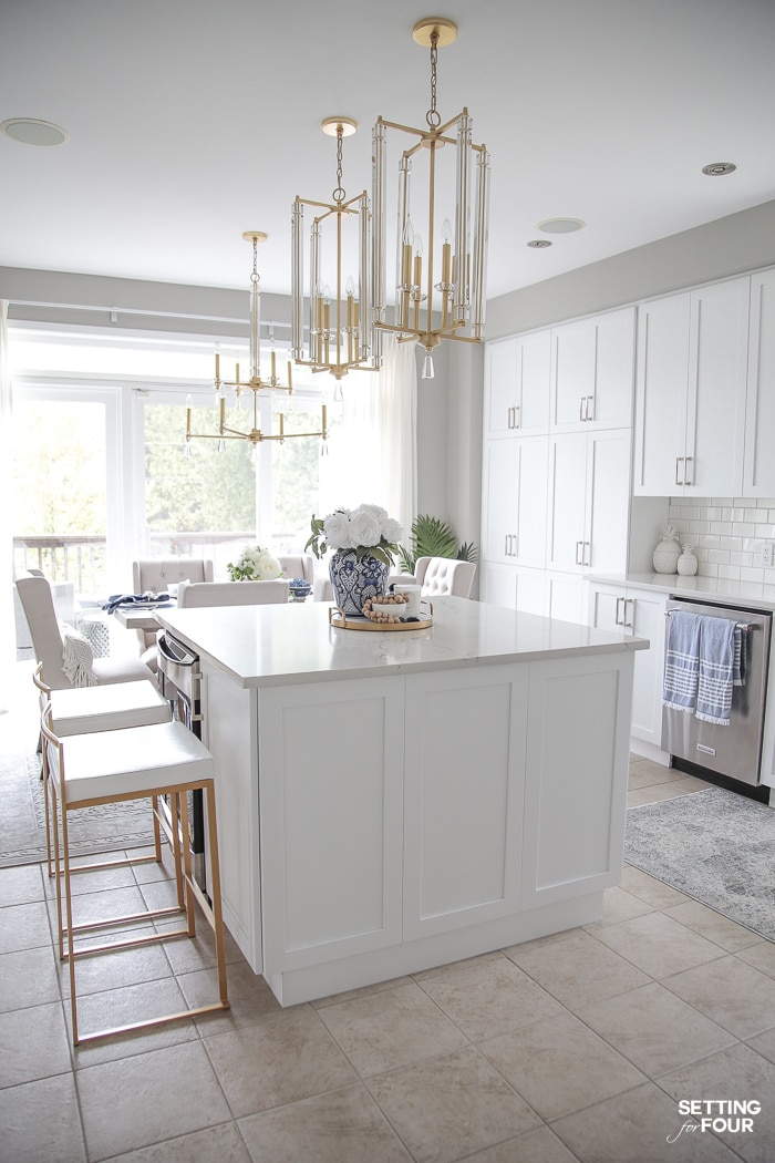 White kitchen cabinets and brass and crystal pendant lights