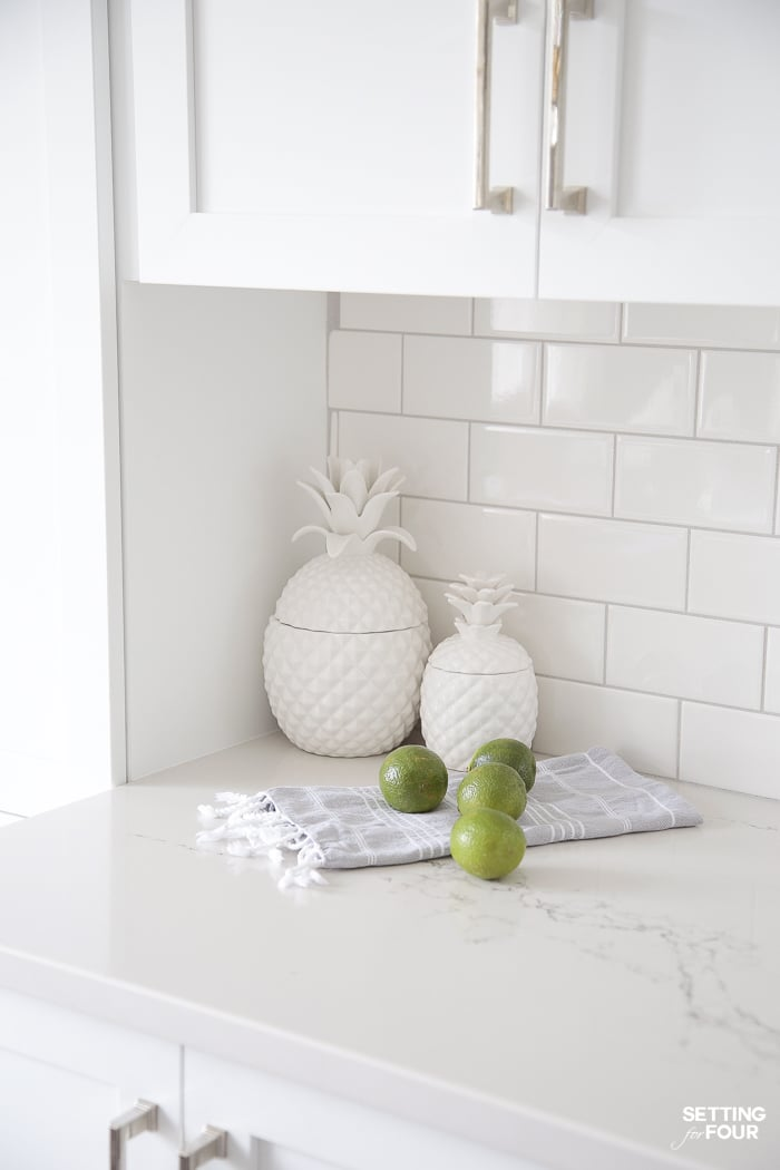 White ceramic pineapple canisters on a kitchen countertop for storage.