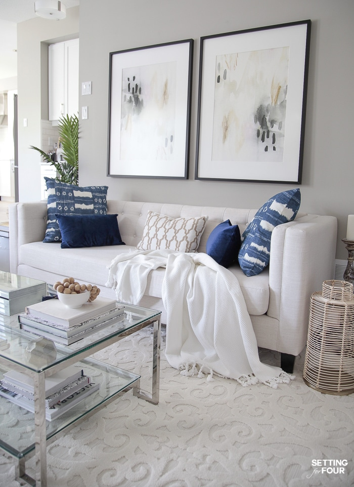 Coastal style living room with two large abstract art pieces hung above the sofa. Blue and white pillows.