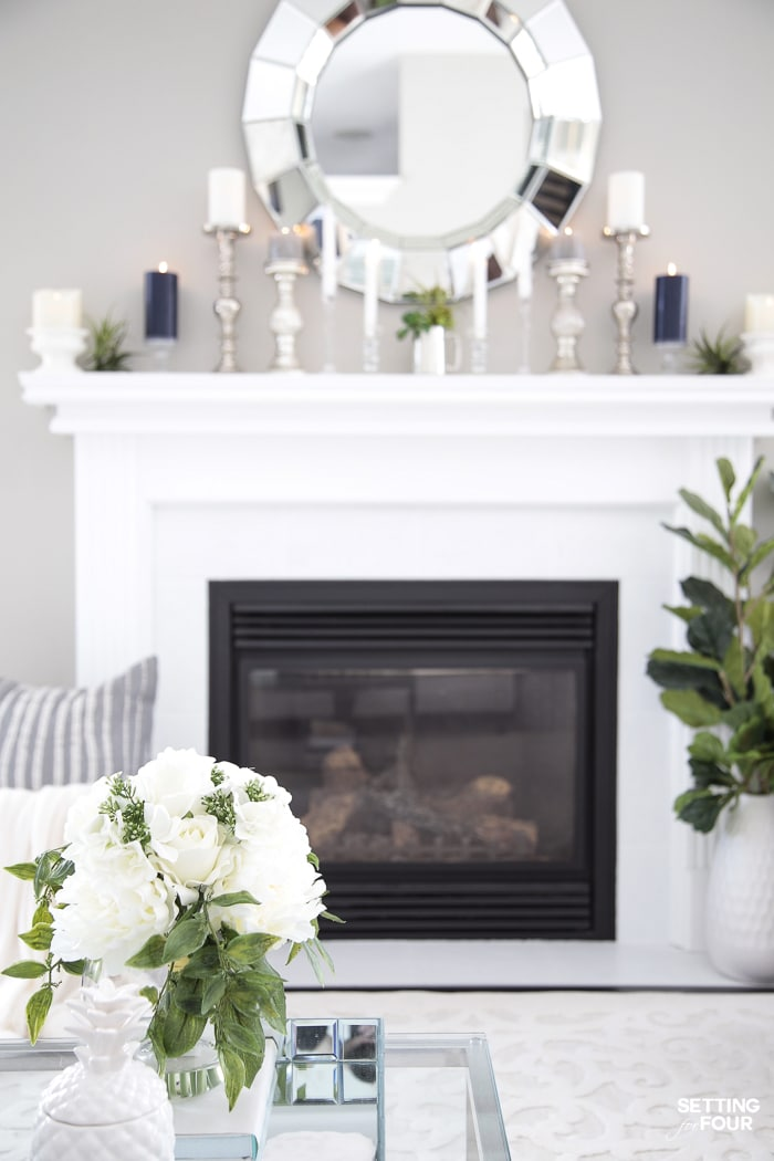 White painted fireplace tile and mantel. Large round mirror over mantel. Summer decor. Candles and air plants on mantel.