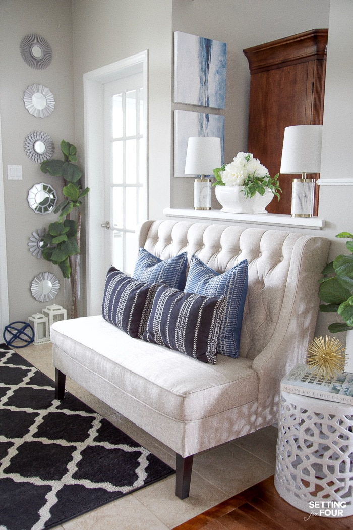 Entryway with bench, black trellis rug, blue and black pillows, coastal art and white garden stool