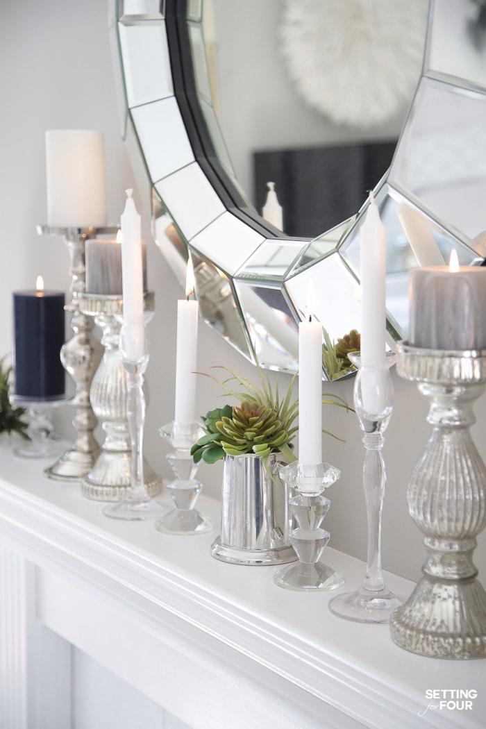 Round mirror hung over white fireplace mantel with candlesticks and candles.