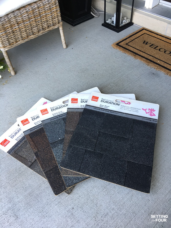 5 large shingle samples from a supplier laid on the front step of a home to choose the perfect roof color.