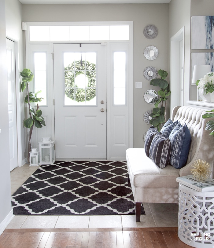 A birght entryway with area rug, plants, setee for seating and blue pillows for color and pattern
