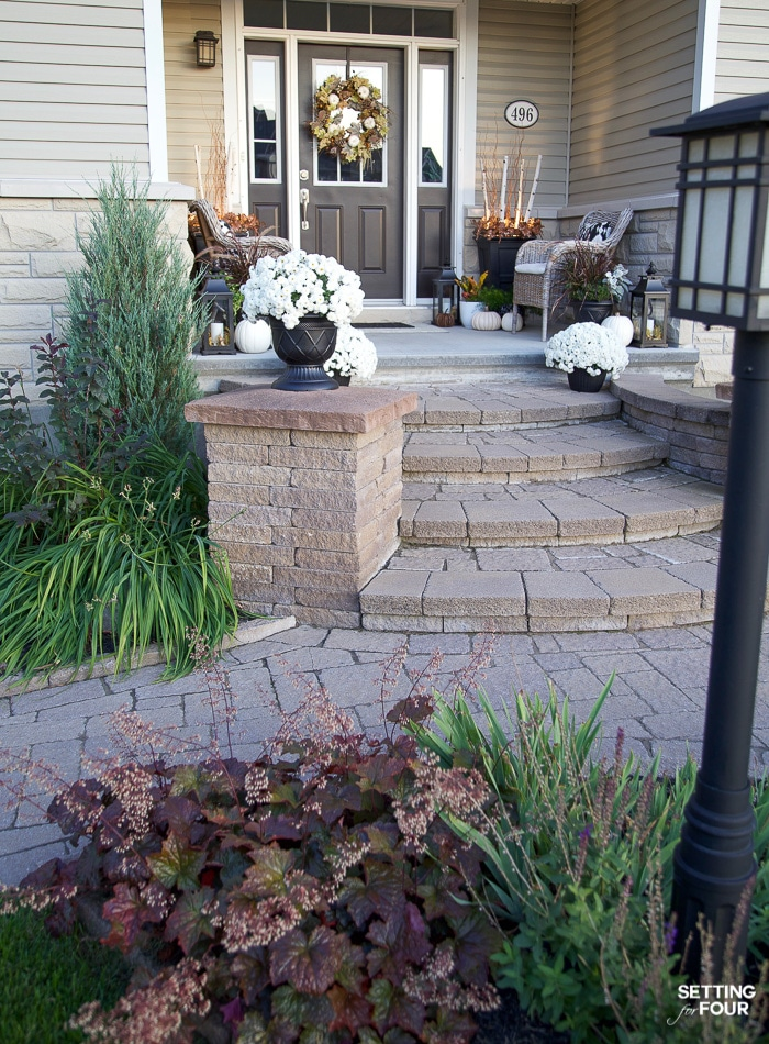 Front of house with stone steps. Decorated for fall with mums and a wreath. Flower bed with heuchera plants.