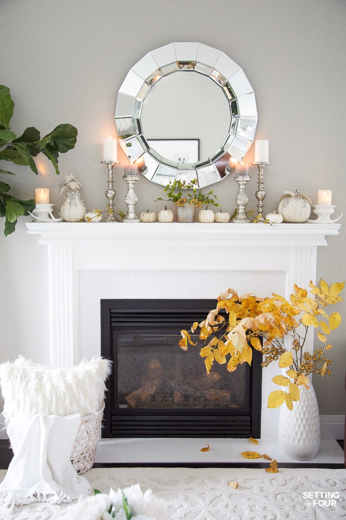 Round faceted mirror above a fireplace mantel in a living room.
