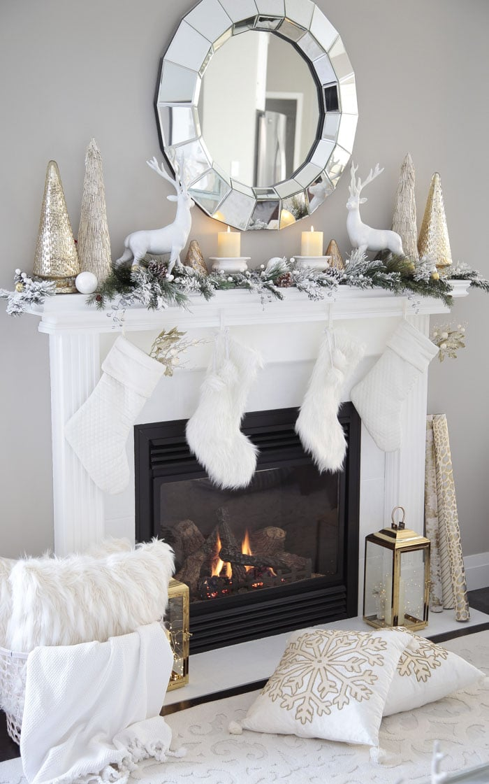 Christmas mantel decor with reindeer, garland and glass Christmas trees.