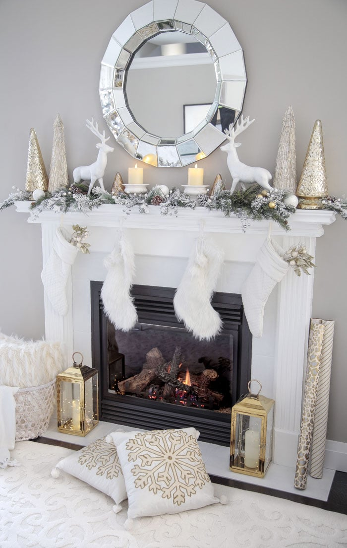 Gold and White Living Room Fireplace Mantel Decor Ideas with Christmas stockings, lanterns and fairy lights.