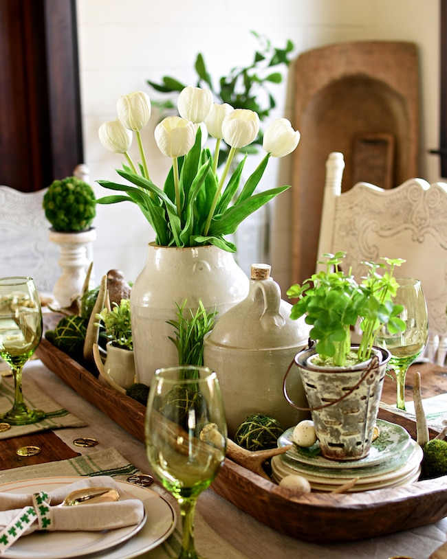 Rustic farmhouse St. Patrick's Day tablescape idea with moss balls and shamrock plant centerpiece.