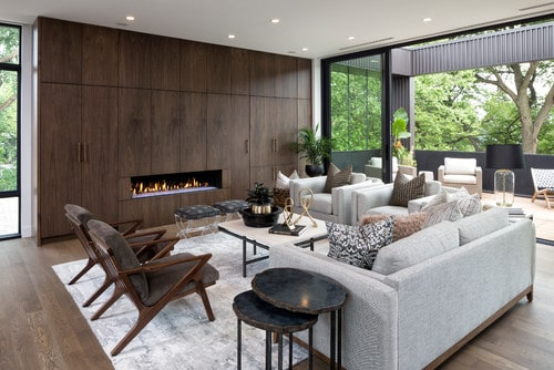 Sofa and four chairs arranged in an open concept living room with fireplace.