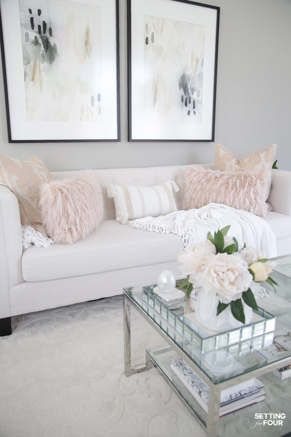 White sofa with blush pink pillows and wall art in living room
