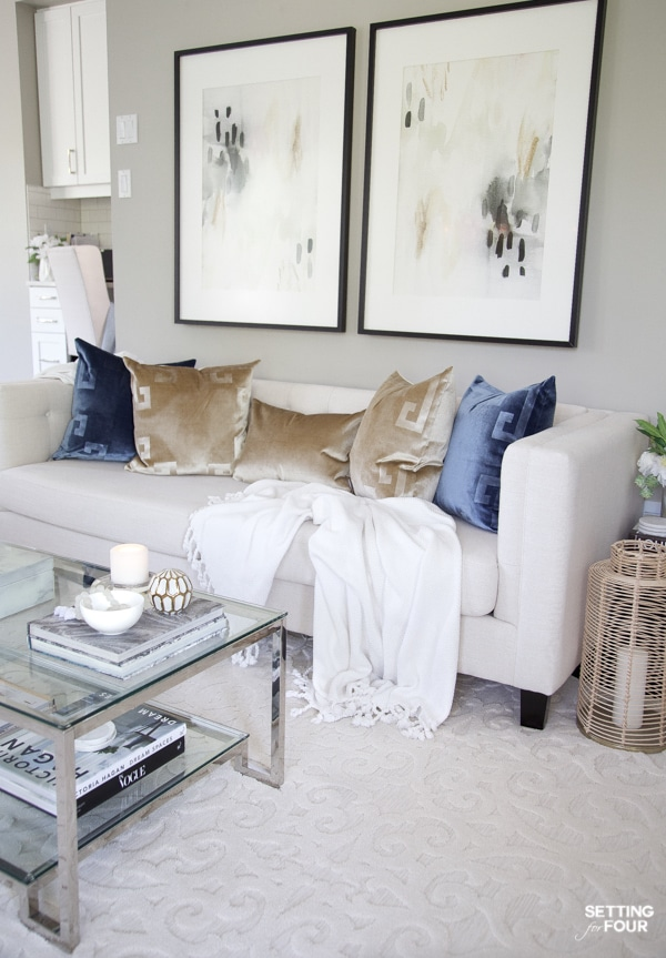 Living room sofa with greek key pillows in gold and blue, abstract wall art and glam coffee table.