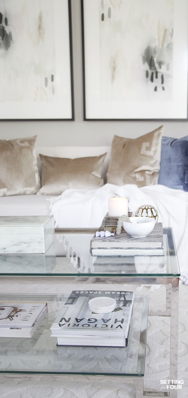 Summer coffee table decorating ideas with coffee table books, tray, decorative box and white and gold sculpture decor in living room. Sherwin Williams Mindful Gray paint color on walls