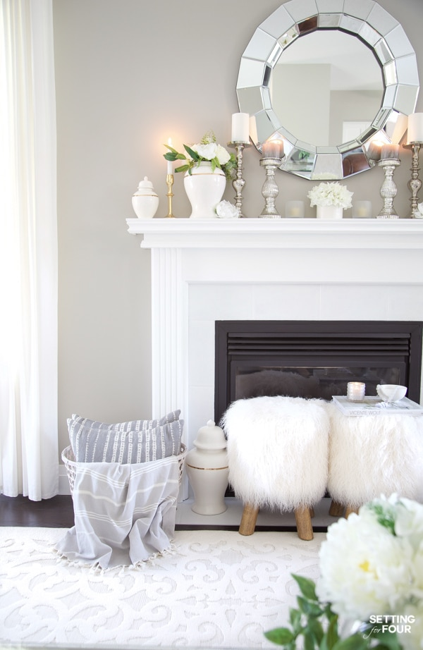 Fireplace mantle decorated for summer with white ginger jars, candles, mirror