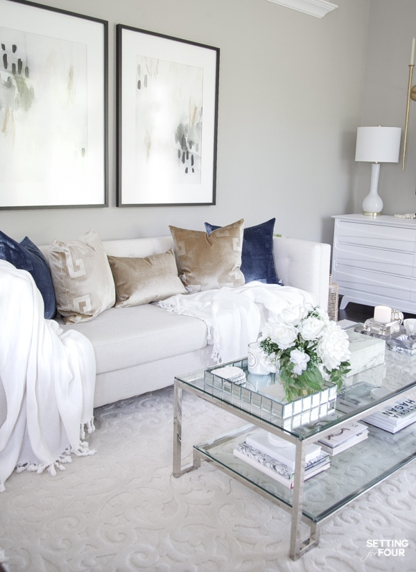 Summer living room decorating ideas with blue and gold pillows, white throw blankets, abstract wall art, coffee table decor. Sherwin Williams Mindful Gray paint color on walls